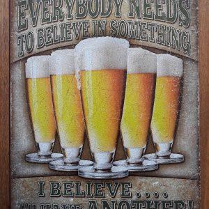 Metalen wandbord - EVERYBODY NEEDS TO BELIEVE IN SOMETHING
